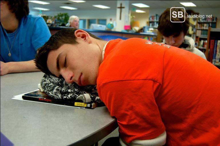 Schüler in der Hauptschule der schlafend mit dem Kopf auf der Schulbank liegt mit Büchern als Kopfkissen