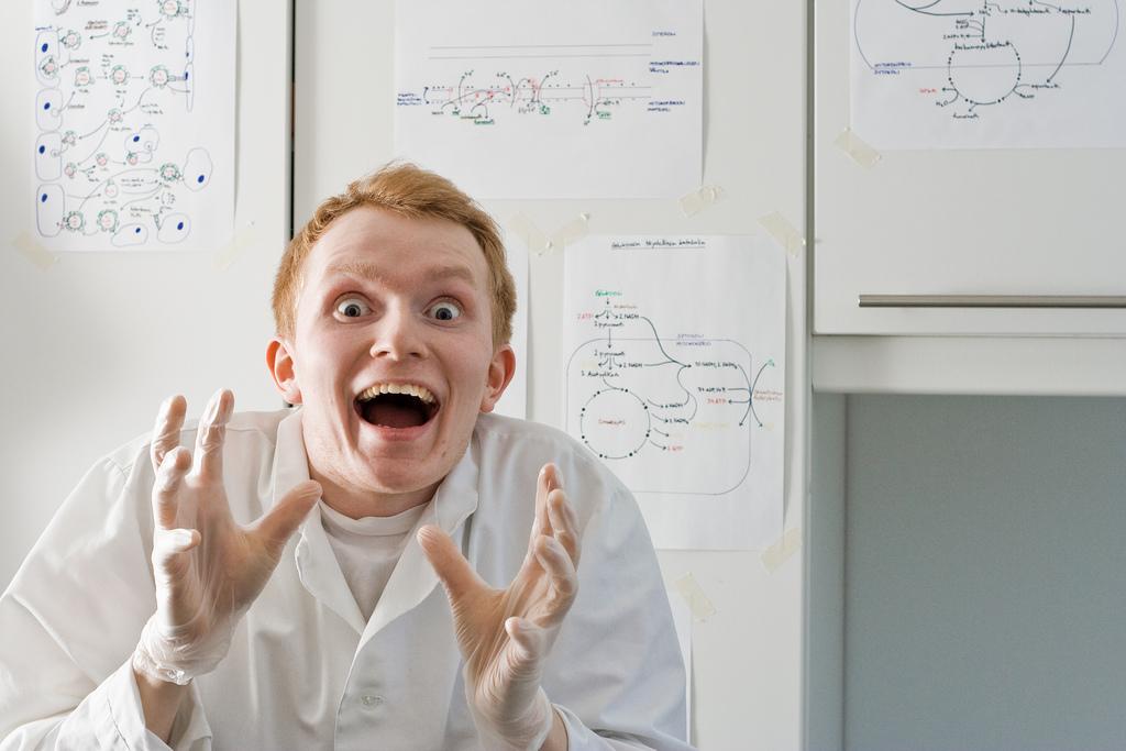 Bild eines Studenten im Labor in Laborkittel der verrückt schaut