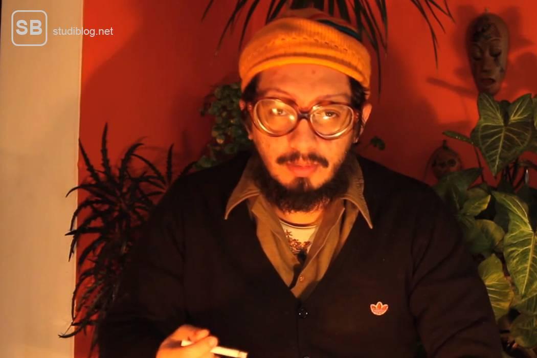 Chilenischer Student mit Brille und Mütze vor der Kamera sitzend. Er erklärt im Video warum und wie er seinen Kommilitonen von insgesamt 500 Millionen Dollar Studiengebühren bzw. Schulden befreit hat indem er Schuldscheine verbrannte
