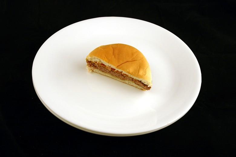 Ein halber Cheeseburger auf einem weißen Teller zum Thema Kalorien verschiedener Produkte