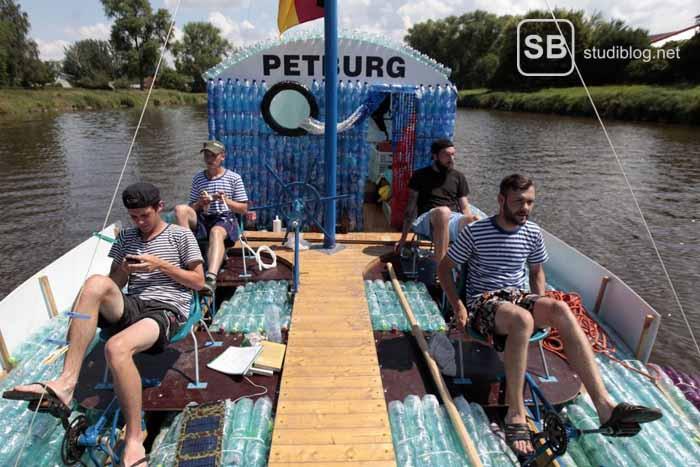 Studenten, die mit einem Boot aus Plastikflaschen fahren