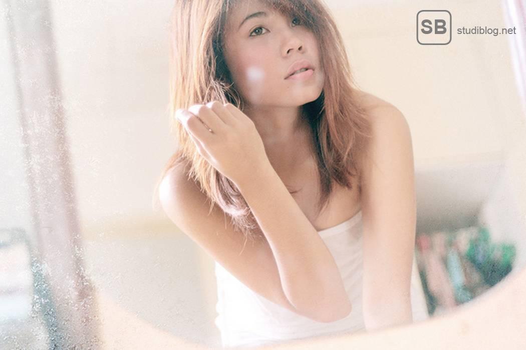 Können mich meine Eltern eigentlich verstehen, fragt sich eine Studentin mit braunen Haaren vor dem Spiegel stehend