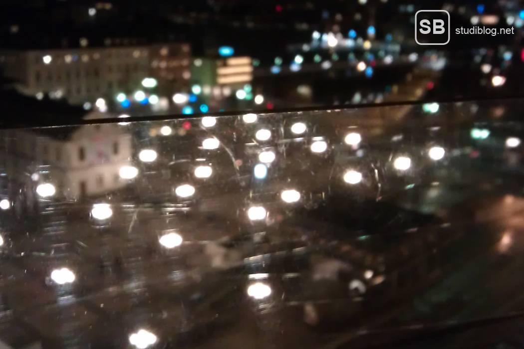 Impressionen im Auslandsstudium - Lichter über den Dächern der Stadt, durch ein gläsernes Geländer hindurch fotografiert bei Nacht