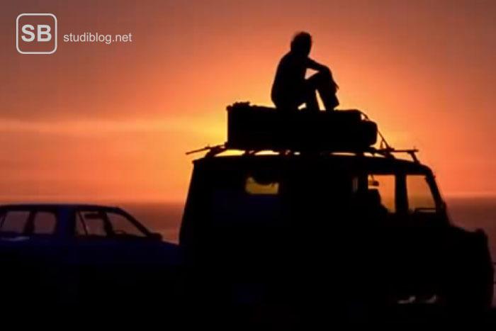 Eine Person auf ihrem Roadtrip bei Sonnenuntergang