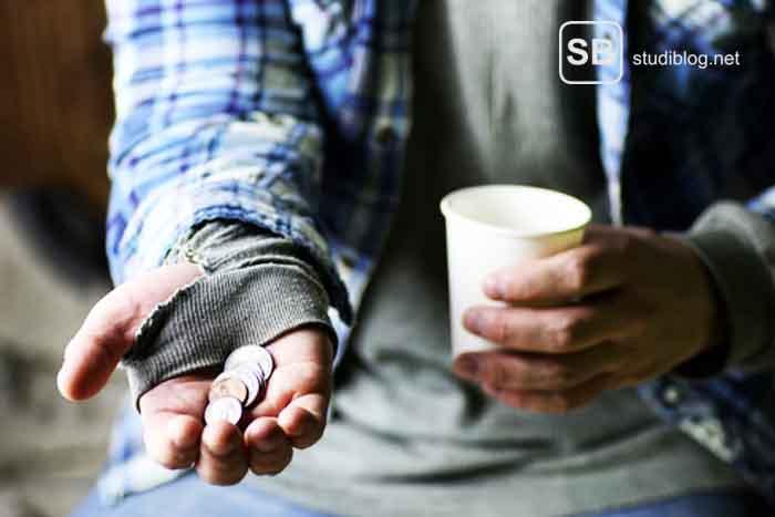 Bettlerhand mit ein paar Münzen und einem Becher zum Thema warum sich Studenten oft unter Wert verkaufen