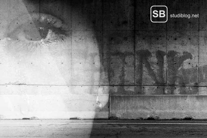 Graue Beton-Mauer mit einem Gesicht zum Thema Depression