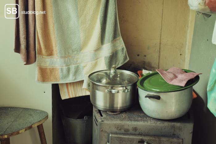 Adieu Hotel Mama - Ungewaschene Töpfe auf einem alten, staubigen Ofen.