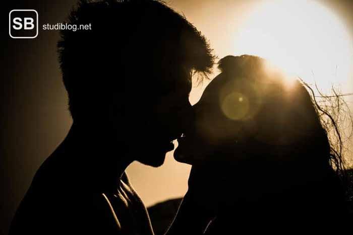 Die Suche nach einem Partner symbolisiert durch ein küssendes Paar im Gegenlicht der Sonne