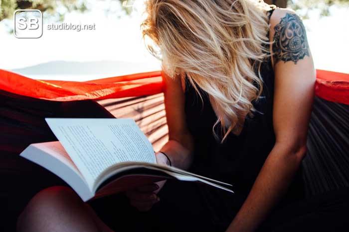 Ein Mädchen in einer Hängematte mit einem Buch in der Hand statt einer Karteikarte