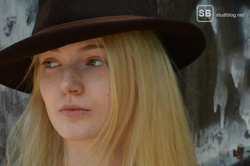 Dating-Orte: Dating Profis sprechen Frauen an diesen 5 Orte nicht an - Das Bild zeigt eine junge, blonde Frau mit Hut und kühlem Gesichtsausdruck
