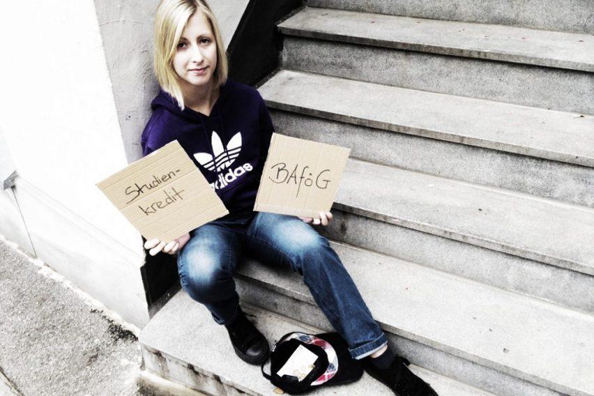 Die Junge Dame hält zwei Schilder hoch, auf denen die Möglichkeiten stehen wie du ein Studium finanzieren kannst.