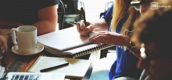 Prokrastination besiegen: Studenten sitzen um Tisch