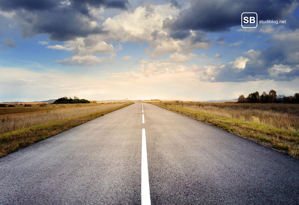 Ziele erreichen: Leere Straße in der Landschaft und blauer Himmel mit Wolken.