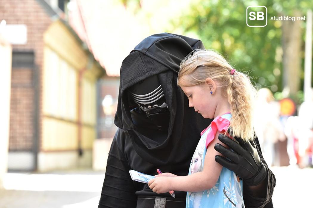 Bild mit einem Mädc hen und einer kostümierten Figur aus einem online Game