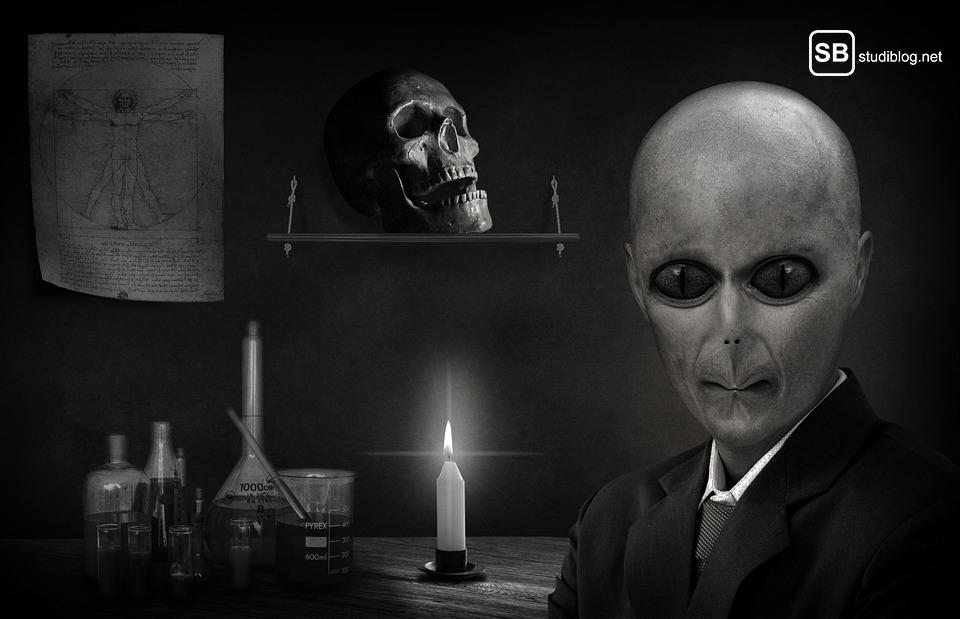 Verschwörungstheorien: Alien im Vordergrund, Kerze, Totenkopf etc. im Hintergrund