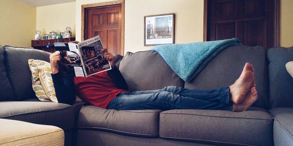 Selbstständig: Mann genießt seinen Feierabend bei einem Magazin auf der Couch