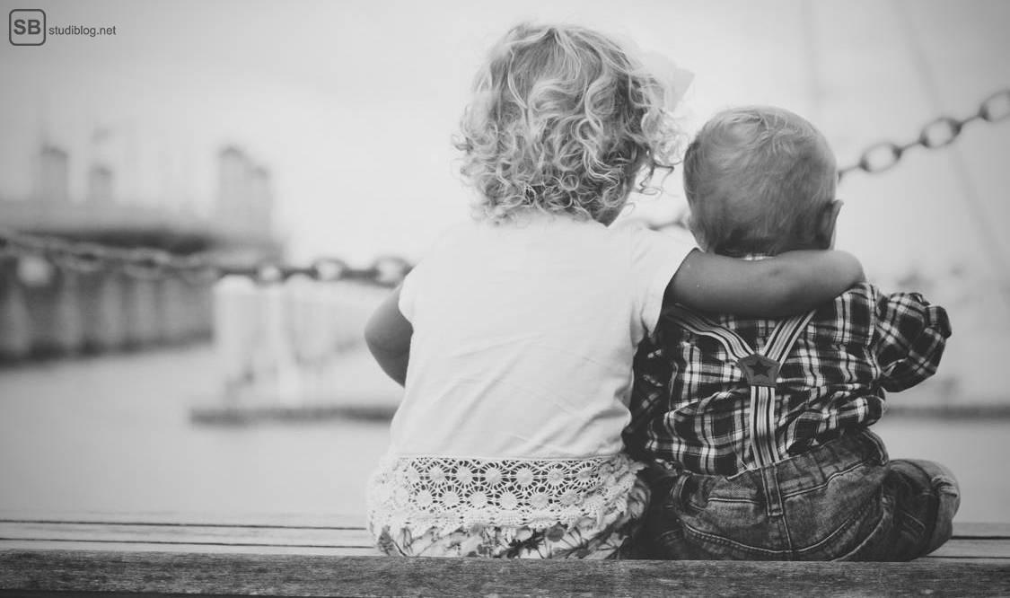 Schwester und Bruder sitzen nebeneinander.