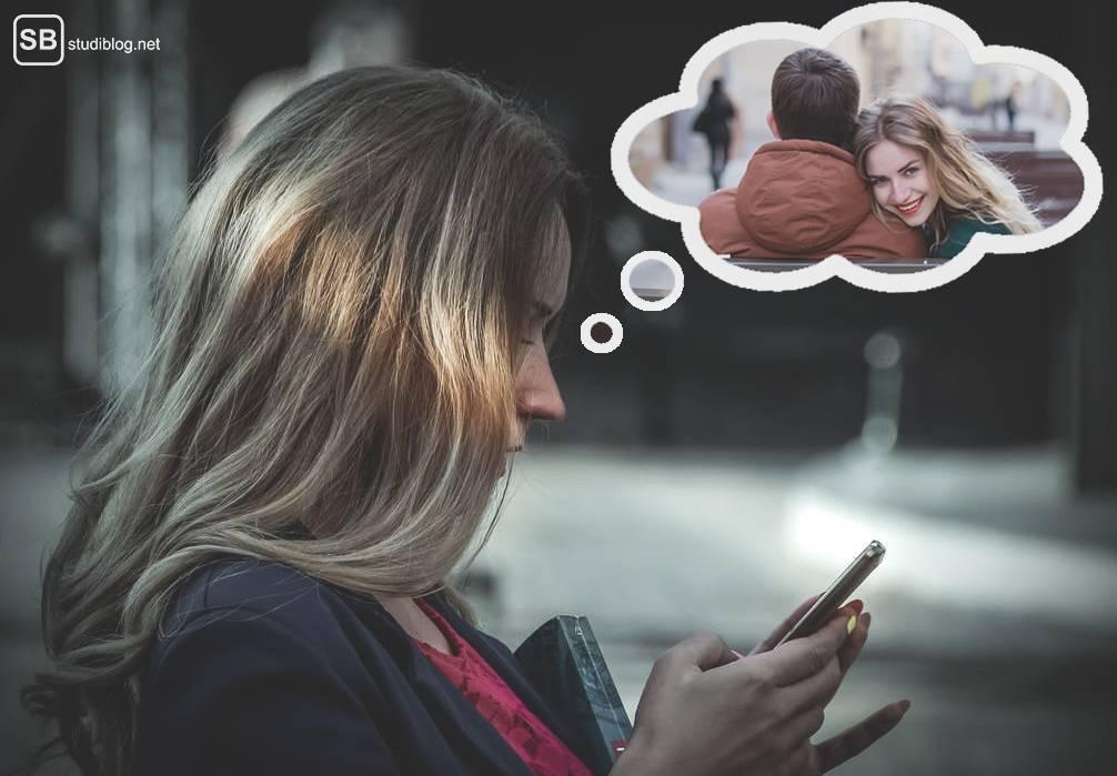 Tinder: Junge Frau mit Handy in der Hand denkt an sich mit einem Partner.