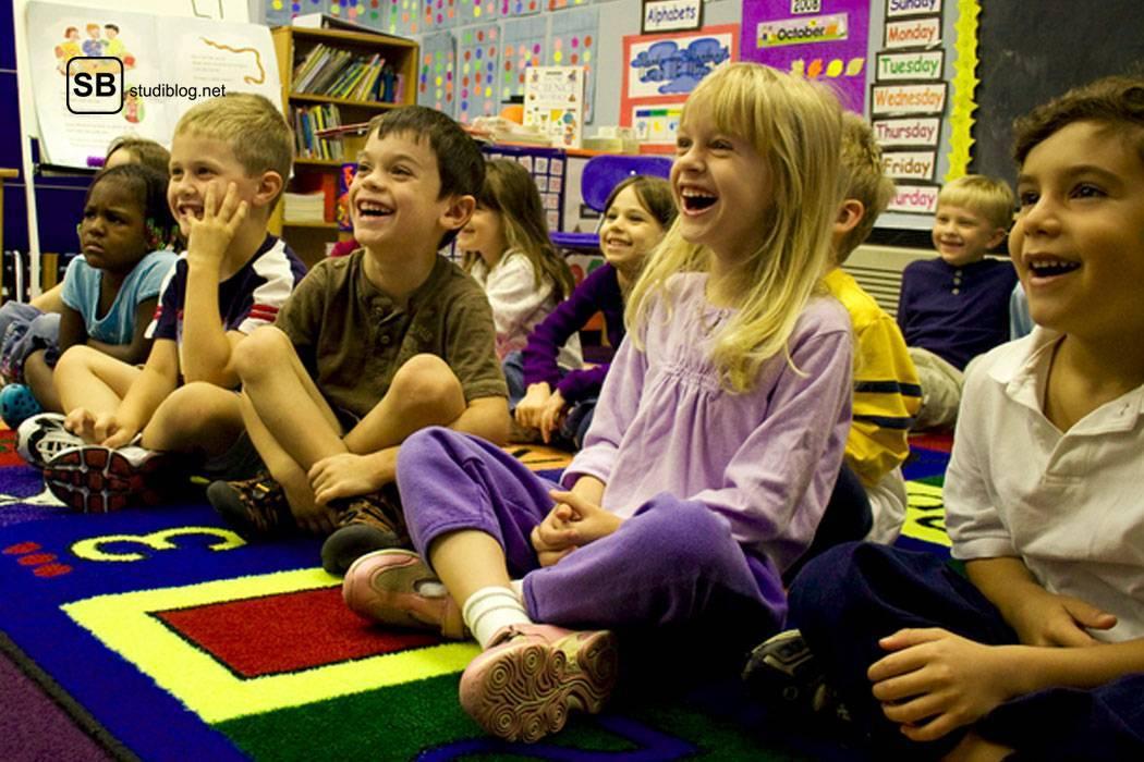 Kindergartenkinder sitzen im Gruppenraum am Teppichboden und lachen über etwas - symbolisch für den Ersti.