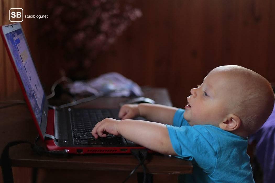 Kleiner Junge steht vor einem auf dem Tisch stehenden Laptop und tippt darauf herum - Studieren mit Kind.