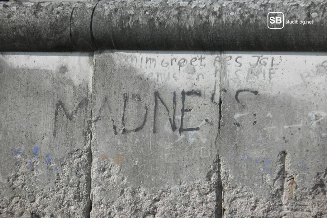 Betonmauer in Berlin auf die der Schriftzug 'MADNESS' gesprayd wurde - den Korrekturleser mit ungenauen Angaben in den Wahnsinn treiben.