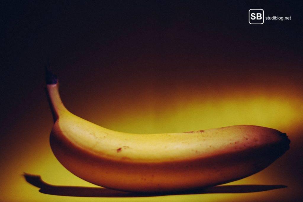 Liegende reife Banane in dunkler Umgebung - Banane essen hilft gegen Sodbrennen: Bindet Magensäure und enthält viel Kalium zur pH-Wert Anpassung.