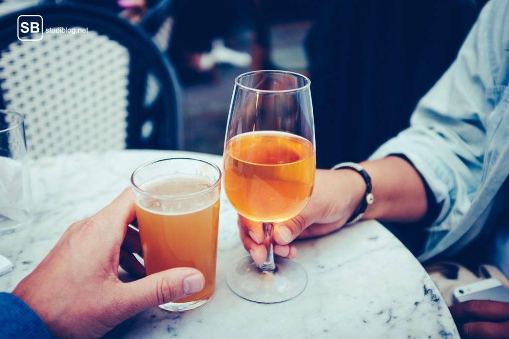 Zwei Leute von denen man nur die Hände sieht stoßen mit orangen alkoholischen Getränken an - Alkohol kann Sodbrennen verursachen.
