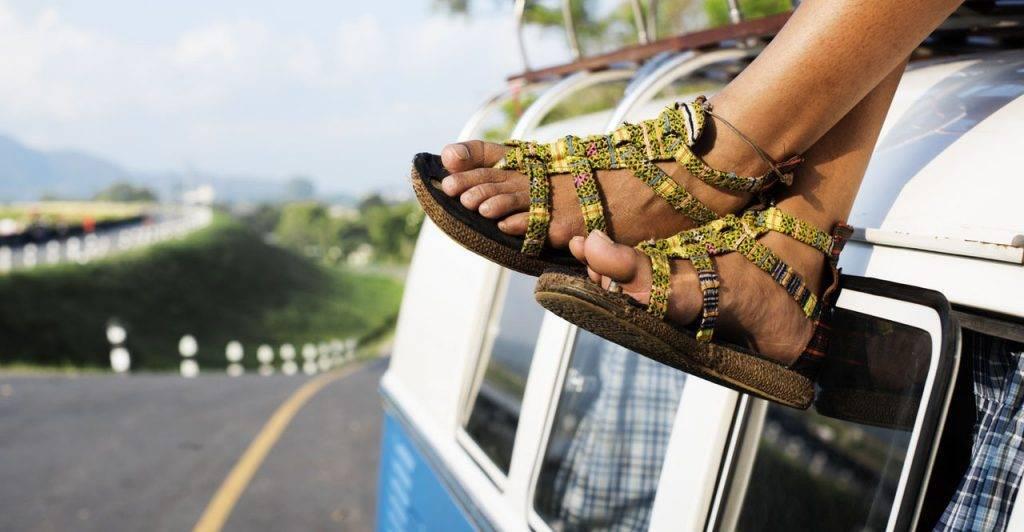 Semesterferien nutzen und reisen: Füße in Sandalen baumeln von einem VW-Bus
