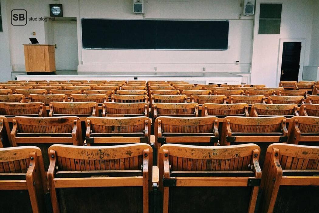 Älterer Hörsaal mit erhöhtem Podest für den Dozenten und typischen Klappstühlen aus Holz - die Bildungswissenschaftsdozentinnen.