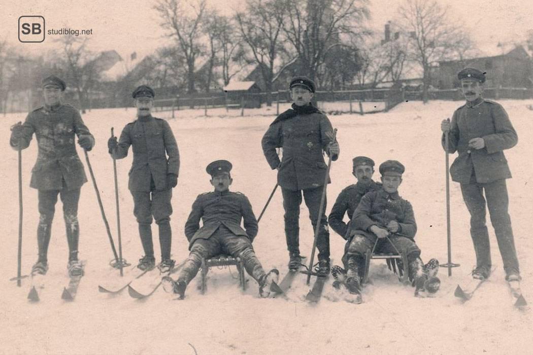 Vergilbtes Schwarz-weiß Foto von jungen Männern auf Skiern stehend und auf Schlitten sitzend - der Geschichtsstudent.
