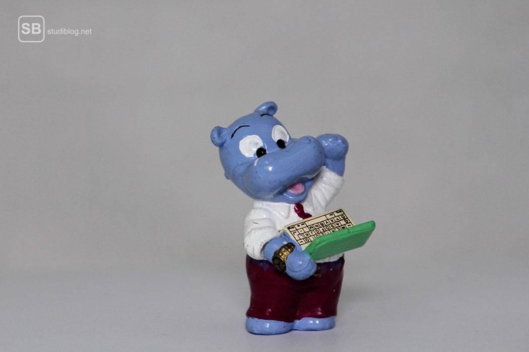 Ein Happy Hippo Nilpferd aus einem Überraschungsei tippt auf einem Laptop rum, den er in einer Hand hält - der Informatikstudent.