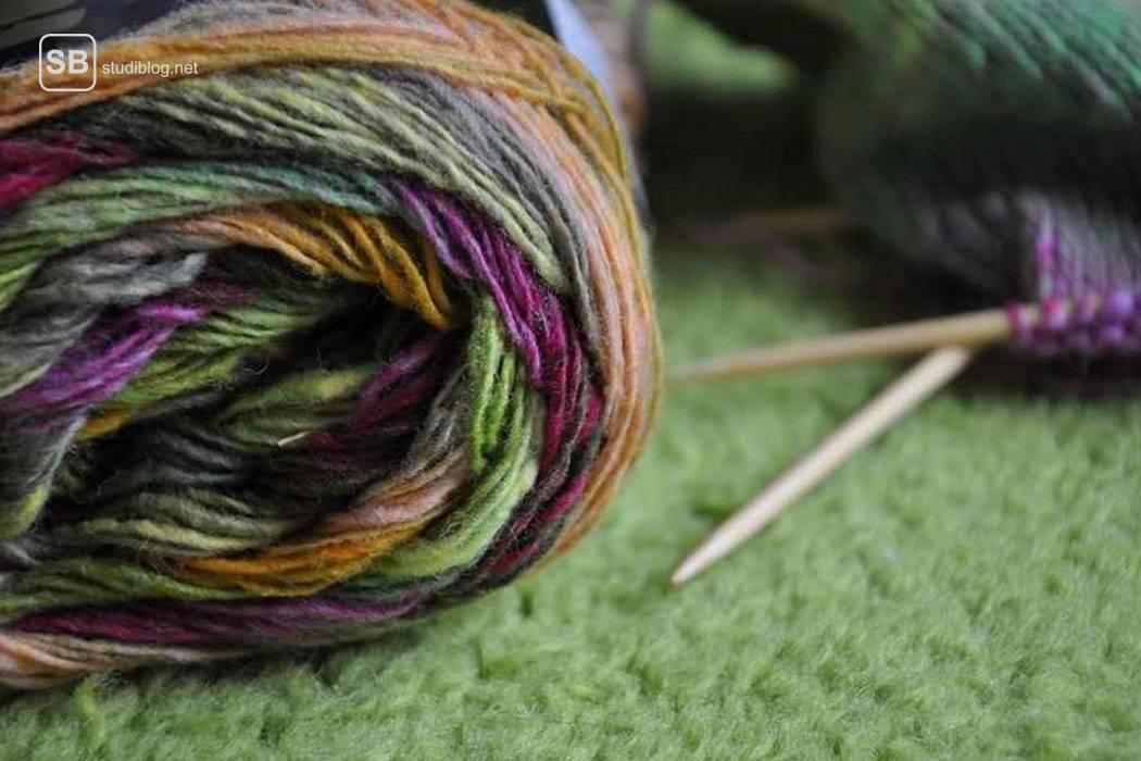Farbiges, noch aufgewickeltes Wollknäuel liegt neben fast fertig gestrickten Socken - der Textilgestaltungsstudent.