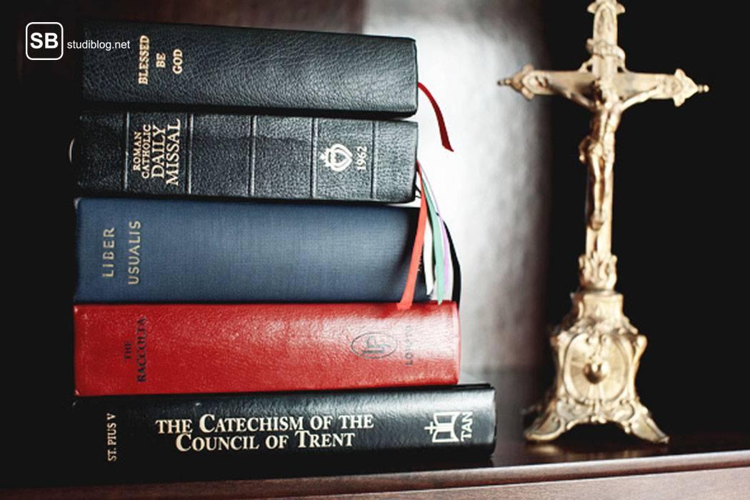 Stapel aus christlichen Büchern - unter anderem auch die Bibel - und rechts davon steht ein Kreuz mit daran genageltem Jesus - der Theologiestudent.