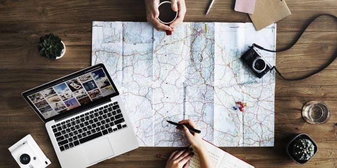Günstige Reise buchen: Mann und Frau sitzen über einer Karte und planen ihren Urlaub