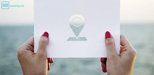 Reise-Ziel: Frau hält Blatt Papier mit einer Kartenmarkierung vors Meer - günstige Reise für Studenten