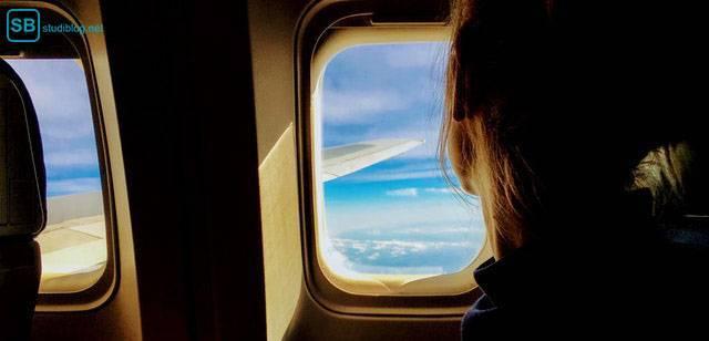Frau blickt aus einem Flugzeug-Fenster - günstige Reise für Studenten