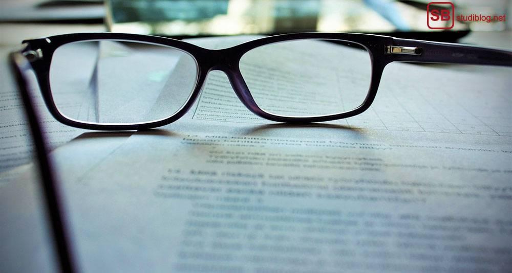 Lektor/Korrekturlesen Bachelorarbeit mit Mentorium: Brille liegt auf einem gedruckten Dokument