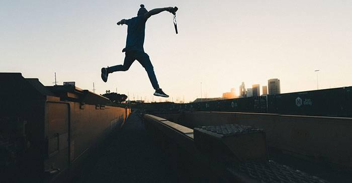 Nostalgie: Junger Mann mit einer Kamera in der Hand springt von einem Waggon auf einen anderen