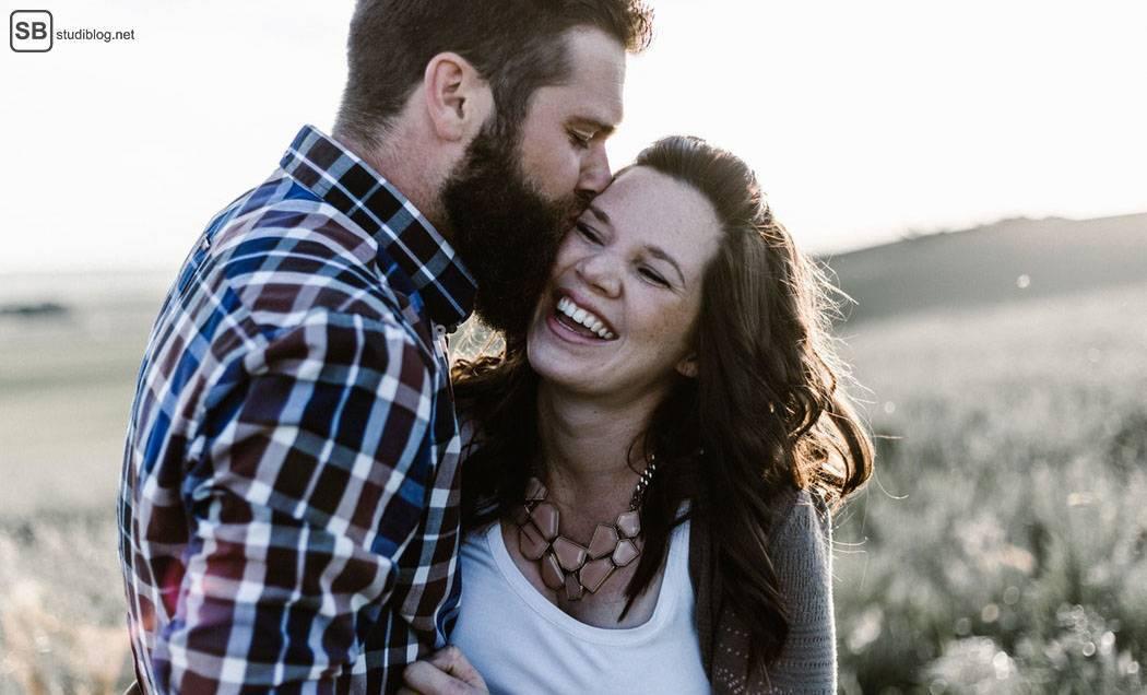 Die große Liebe über online-Dating: Mann küsst lachende Frau auf die Wange