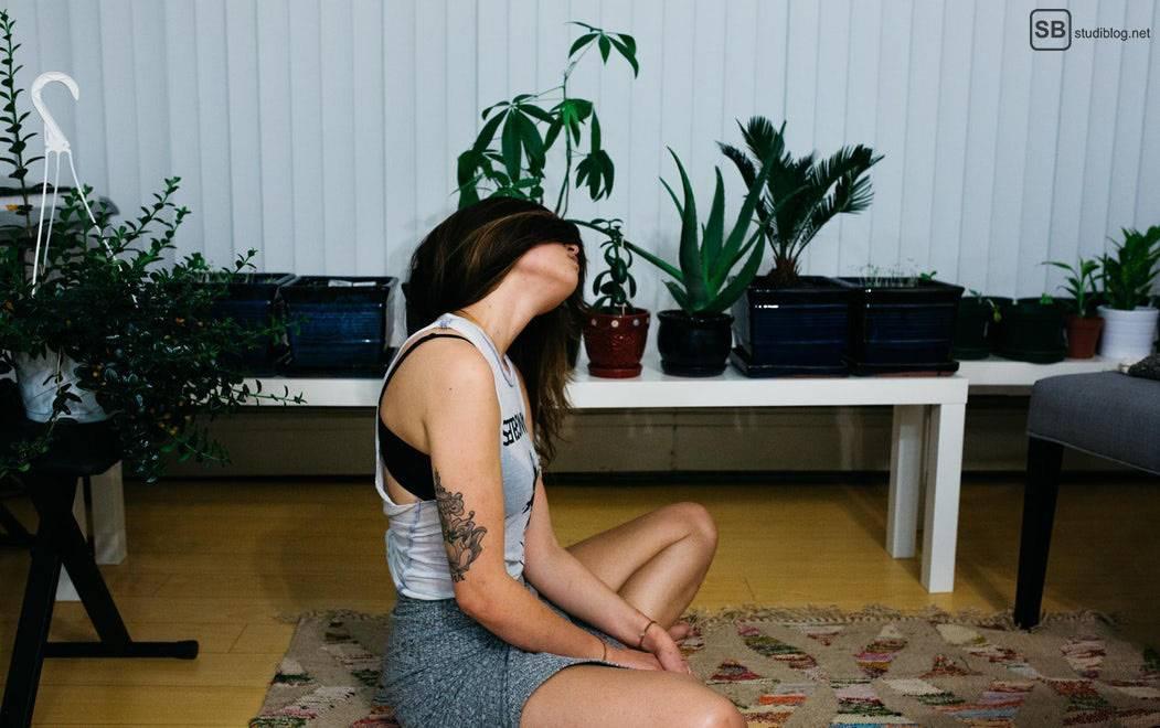 Das Schöne am Studieren: Studentin sitzt im Wohnzimmer auf dem Boden mit ihren Haaren im Gesicht