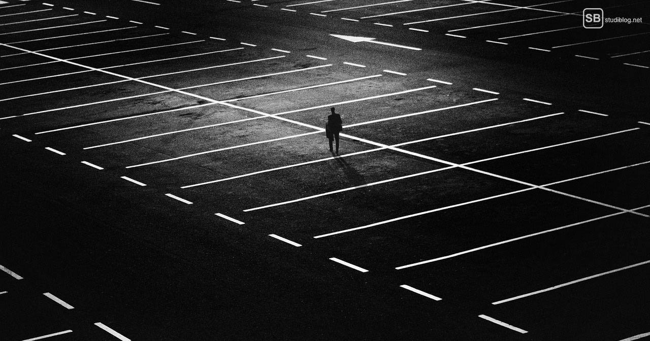 Depression: Mann läuft nachts alleine über einen großen Parkplatz