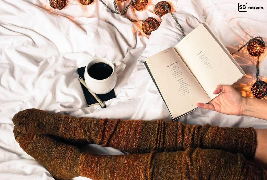 Hygge als Lebensgefühl: Mädchen sitzt in dicken Kniestrümpfen im Bett mit einer Lichterkette, einem Kaffee und einem Buch