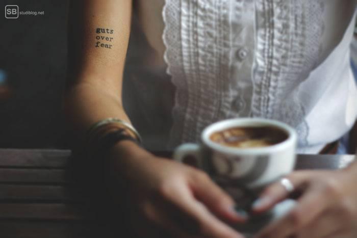 Veränderung: Frau sitzt in einem Café mit einem Kaffee in der Hand und hat auf den Arm tätowiert: guts over fear