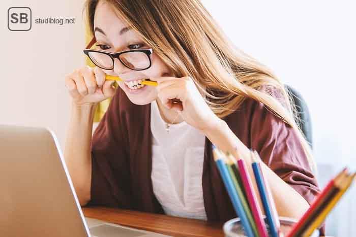 Ich und wissenschaftliches Arbeiten - Mädchen vorm Rechner dass auf Stiften herum beißt