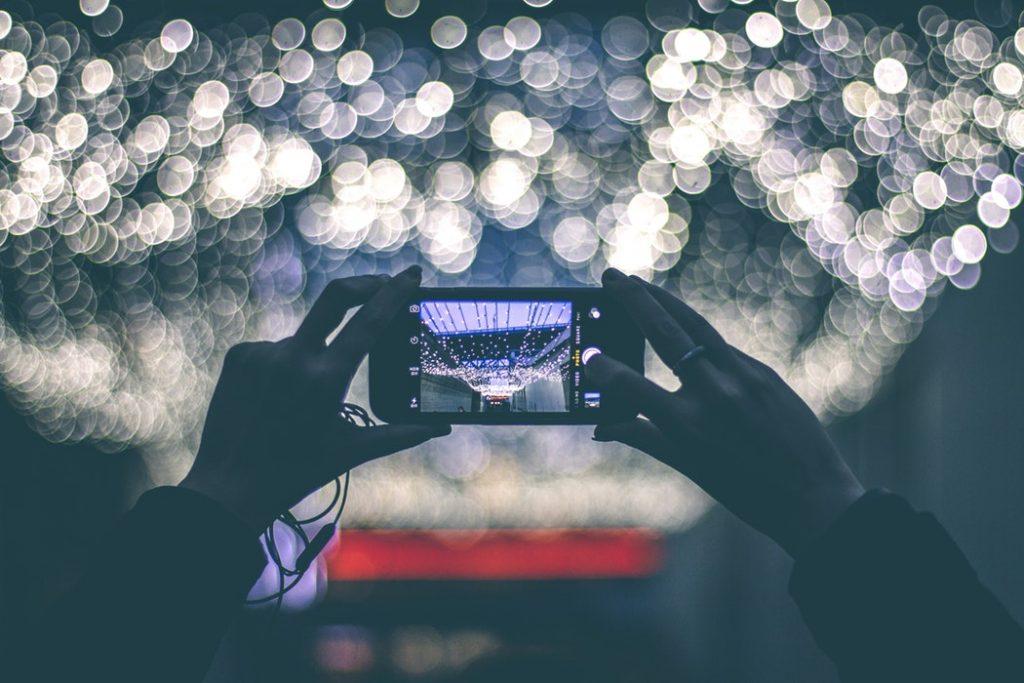 Tipps für bessere Fotos mit dem Smartphone: Frau fotografiert eine Lampe