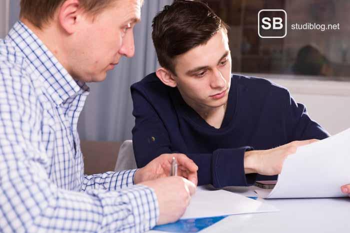 Herausforderungen im Studium für Minderjähriger - Vater mit seinem Sohn am Tisch sitzend wegen einer Unterschrift