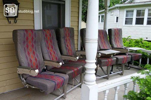Auf einer Veranda stehen statt einer Sitzgarnitur 6 alte Flugzeugsitze - Dinge, die arme Studenten machen.