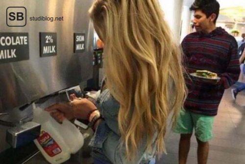 Mädchen mit blonden Haaren füllt Milch in einen Kanister in der Mensa - Dinge, die arme Studenten machen.