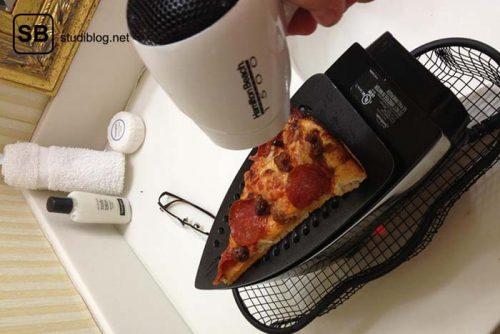 Pizza liegt auf der heißen Seite eines eingeschalteten Bügeleisen und wird von oben von einem Föhn erhitzt - Dinge, die arme Studenten machen.