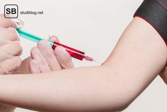 Behandschuhte Hände vollziehen die Blutabnahme in der Ellbogenbeuge bei einer Patientin.